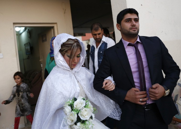 Displaced Iraqi Shi'ite Muslim Mohammed Harith Youssif (R), 25, walks with his 20-year-old bride Reem Ahmed (R), a Sunni Muslim who fled from the violence in Mosul, during their wedding at a school in Baghdad. The Sh'ite Muslim man married his Sunni Muslim bride in Baghdad on Monday, after the couple had fled violence by Islamic State militants in their home town of Mosul. (Thaier Al-Sudani/Reuters)