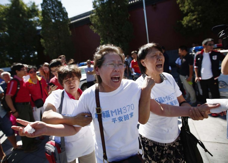 Family members of passengers onboard the missing Malaysia Airlines Flight MH370, cry as they gather to pray Yonghegong Lama Temple in Beijing September 8, 2014, on the six-month anniversary of the disappearance of the plane. The Boeing 777 aircraft carrying 239 passengers and crew, disappeared on March 8 after taking off from Malaysia's capital, Kuala Lumpur, bound for Beijing. About two thirds of those on board were from China. (Kim Kyung-Hoon/Reuters)