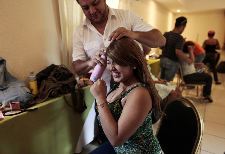 "Levis, a volunteer stylist, puts a wig on a cancer patient during the preparation for her ""Quinceanera"" (15th birthday) party at a hotel in Managua September 20, 2014. A quinceanera is a traditional celebration for a girl turning 15. The Nicaragua's Association of Mother and Father of Children with Leukemia and Cancer (MAPANICA) organizes quinceaneras for cancer patients annually, and there were 44 celebrants in 2014. Picture taken September 20, 2014. (Oswaldo Rivas/Reuters)"