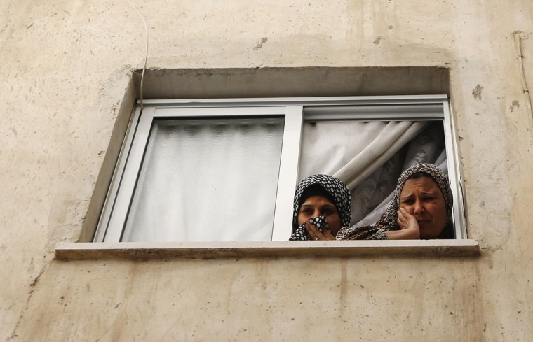 Women mourn as they watch from a window the funeral of Issa al Qitri, a Palestinian man who was killed by Israeli troops, at al-Amari camp near the West Bank city of Ramallah September 10, 2014. Israeli troops shot and killed 22-year-old Qitri on Wednesday during a raid on a West Bank refugee camp, Palestinian medics and the Israeli military said. The soldiers, seeking to detain a Hamas militant, were confronted by around 50 Palestinians who hurled stones, petrol bombs and burning tyres at them, an Israeli military spokeswoman said. The spokeswoman said Qitri was shot while trying to throw an explosive device at the soldiers. (Mohamad Torokman/Reuters)