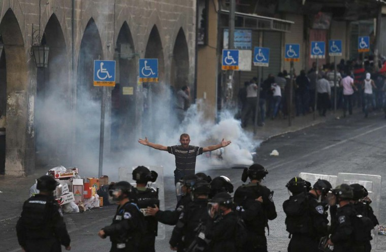 A Palestinian gestures in front of Israeli police during clashes that broke after the funeral of Mohammed Sinokrot outside Jerusalem's Old City September 8, 2014. Scores of Palestinians rioted in East Jerusalem for a second day after hearing that the youth from their neighbourhood had died of wounds suffered in a clash with Israeli police last week. Sinokrot succumbed to a head wound suffered during a protest a week ago but the circumstances of how he sustained the wound were in dispute. (Ammar Awad /Reuters)