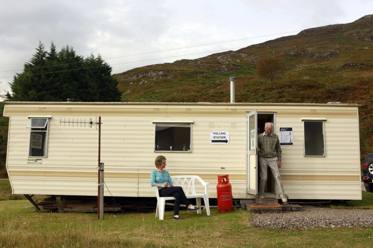 Presiding officer Anne MacKay (L) and her father and Poll Clerk George MacKay are seen outside the Coulags caravan polling station, in the Scottish Highlands September 18, 2014. Polling in the referendum on Scottish independence began on Thursday morning, as Scotland votes whether or not to end the 307-year-old union with the rest of the United Kingdom. (Cathal McNaughton/Reuters)