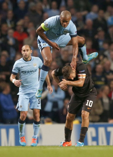 Manchester City's Vincent Kompany (top) challenges AS Roma's Francesco Totti during their Champions League soccer match at the Etihad Stadium in Manchester, northern England September 30, 2014. (REUTERS/Phil Noble)