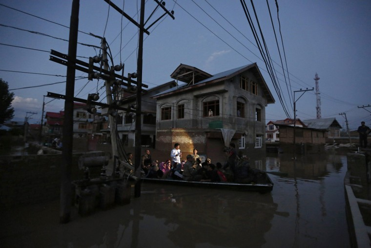 Flood victims are evacuated by boat from their flooded house in Srinagar September 10, 2014. Flood waters started receding in Indian Kashmir on Wednesday, giving rescue teams a chance to reach tens of thousands of villagers stranded by the heaviest rainfall in half a century. Floods and landslides triggered by days of rain in the disputed Himalayan region have killed at least 450 people in India and Pakistan and cut off more than one million people from basic services. (Adnan Abidi/Reuters)