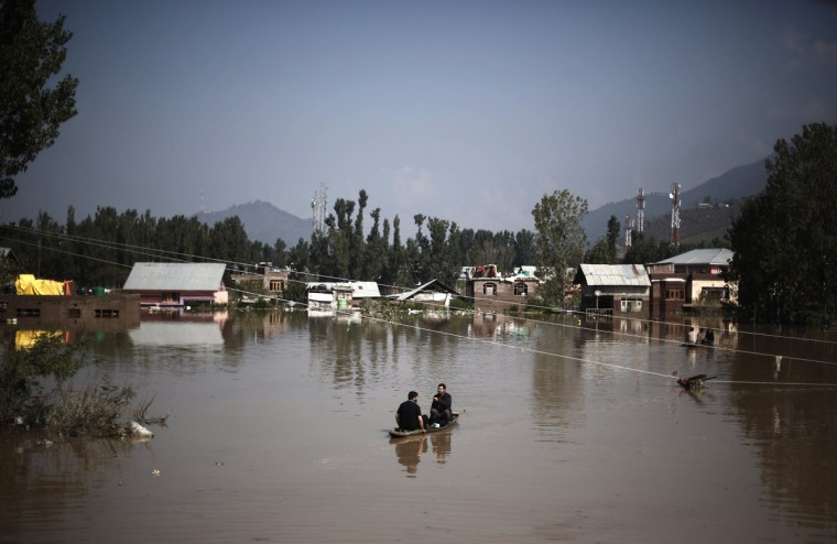 Kashmiri men row a boat to cross the flooded areas as they move toward higher ground in Srinagar September 10, 2014. Flood waters started receding in Indian Kashmir on Wednesday, giving rescue teams a chance to reach tens of thousands of villagers stranded by the heaviest rainfall in half a century. Floods and landslides triggered by days of rain in the disputed Himalayan region have killed at least 450 people in India and Pakistan and cut off more than one million people from basic services. (Adnan Abidi/Reuters)