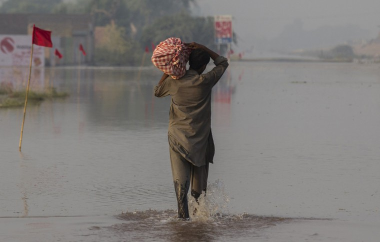 A flood victim wades through a flooded field following heavy rain in Jhang, Punjab province, September 11, 2014. Floods that have killed 450 people in India and Pakistan began to recede on Wednesday giving rescue teams a chance to evacuate thousands of villagers stranded by the heaviest rainfall in 50 years in the heavily militarised and disputed region of Kashmir. REUTERS/Zohra Bensemra