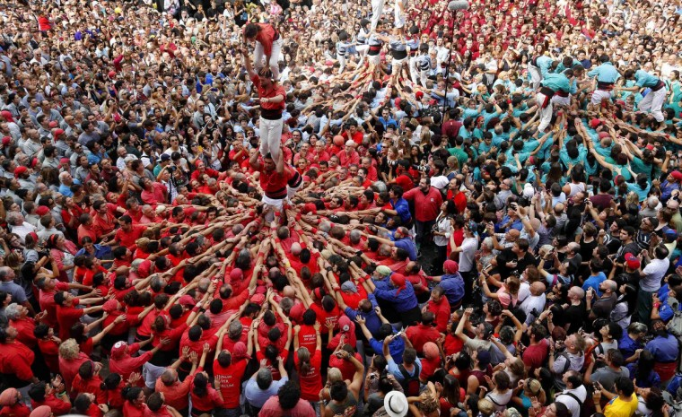 """""""Castellers de Barcelona"""" form a human tower during a demonstration at the festival of the patron saint of Barcelona """"The Virgin of Mercy"""" at Sant Jaume square in Barcelona. (Gustau Nacarino/Reuters)"""