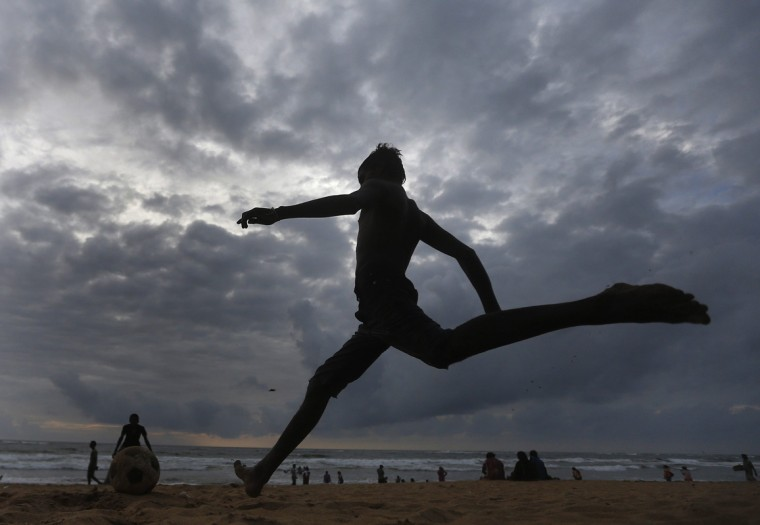 A boy runs to kick a soccer ball on the beach in Colombo September 10, 2014. (Dinuka Liyanawatte/Reuters)