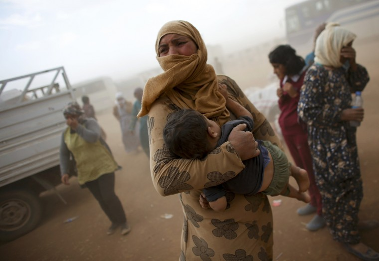 A Kurdish Syrian refugee waits for transport during a sand storm on the Turkish-Syrian border near the southeastern town of Suruc in Sanliurfa province. The United Nations refugee agency said on Tuesday it was making contingency plans in case all 400,000 inhabitants of the Syrian Kurdish town of Kobani fled into Turkey to escape advancing Islamic State militants. (Murad Sezer/Reuters)