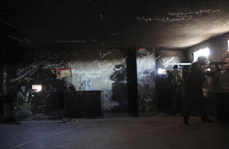 Forces loyal to Syria's President Bashar al-Assad aim their weapons as they take up positions inside the traffic police branch during what they said was an offensive against them by rebel fighters in the Bab al-Jenin neighbourhood of Aleppo September 10, 2014. (George Ourfalian/Reuters)