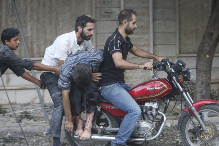Civilians transport an injured man on a motorbike after what activists said were airstrikes by forces loyal to Syria's President Bashar al-Assad, in the Duma neighbourhood of Damascus September 10, 2014. (Bassam Khabieh/Reuters)