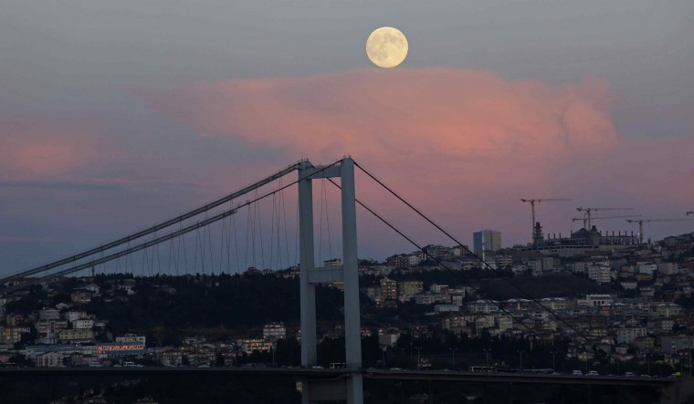 A full moon rises over the Bosphorus bridge in Istanbul September 8, 2014. The September full moon, also known as the Harvest Moon, is the last of this summer's three supermoons, and the final one of the year. (Murad Sezer/Reuters)