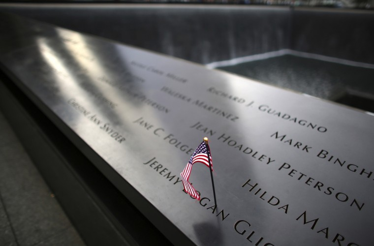 An American flag is seen on inscribed names on the edge of the north pool of the 911 Memorial during memorial observances held at the site of the World Trade Center in New York, September 11, 2014 REUTERS/Chang Lee/Pool