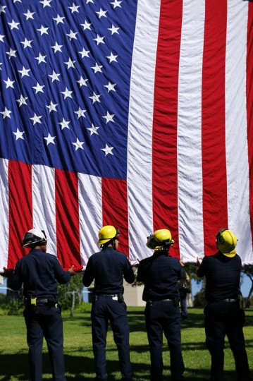 Fire fighters from CAL Fire unfurl a large American flag from a ladder truck during a remembrance event on the campus of Cuyamaca College in El Cajon, California September 11, 2014. Today is the thirteenth anniversary of the 9/11 attacks on New York, Washington, and Pennsylvania. REUTERS/Mike Blake