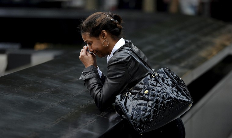 A woman who did not wish to be identified pauses at the edge of the North Pool during memorial observances on the 13th anniversary of the 911 attacks at the site of the World Trade Center in New York, September 11, 2014. Politicians, dignitaries and victims' relatives were gathering in New York, Washington and Pennsylvania on Thursday to commemorate the nearly 3,000 people killed in al Qaeda's attack on the United States 13 years ago on Sept. 11. REUTERS/Justin Lane