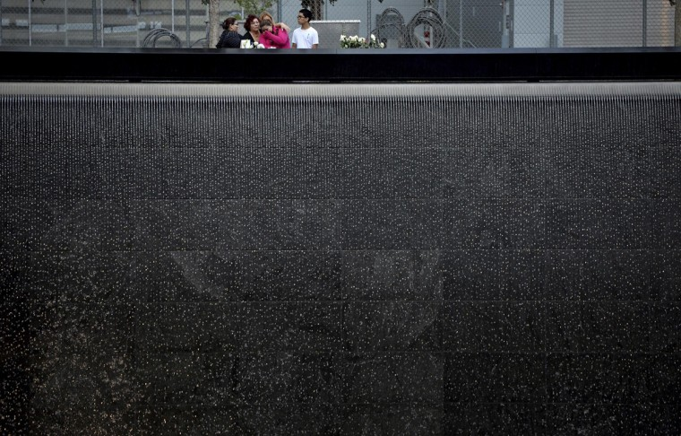 A family stands at the edge of the North Pool during memorial observances on the 13th anniversary of the 911 attacks at the site of the World Trade Center in New York, September 11, 2014. Politicians, dignitaries and victims' relatives were gathering in New York, Washington and Pennsylvania on Thursday to commemorate the nearly 3,000 people killed in al Qaeda's attack on the United States 13 years ago on Sept. 11.REUTERS/Justin Lane