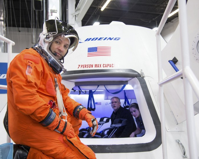 """NASA astronaut Randy Bresnik prepares to enter Boeing's CST-100 spacecraft for a fit check evaluation at the company's Houston Product Support Center in this undated image. NASA will partner with Boeing and SpaceX to build commercially owned and operated """"space taxis"""" to fly astronauts to the International Space Station, ending U.S. dependence on Russia for rides, officials said on Tuesday. (NASA/Handout via Reuters/Reuters)"""