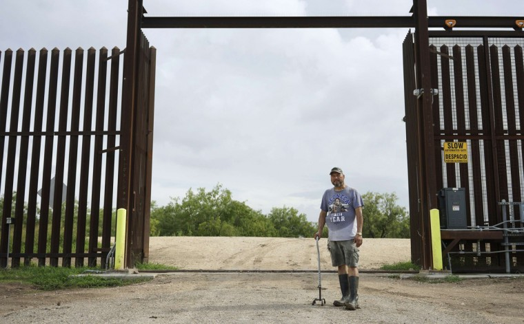 """Fernando Rivera Jr. poses at the open gate of the 18-foot (five-metre) high rusty steel barrier along the U.S.-Mexico border outside Brownsville, Texas September 2, 2014. Fernando says that immigrants regularly stroll through the gate and onto his property. The """"Patriots"""" are a heavily armed group who patrol the U.S. border with Mexico, trying to deter immigrants from crossing the border illegally. The group, who portray themselves as defending the American way, use a strong display of force to intimidate anyone from making the crossing from Mexico into Texas. To critics, they are vigilantes spoiling for a fight. To the immigrants, they are another barrier to entry and to the U.S. Border Patrol, groups like this can either be a nuisance interfering with their operations or an aide in spotting migrants illegally trying to enter the country. Picture taken September 2, 2014. (Rick Wilking/Reuters)"""
