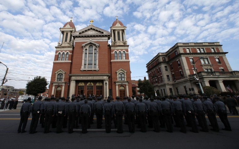 Pennsylvania State Police line the streets outside St. Peter's Cathedral in Scranton, Pennsylvania September 18, 2014, ahead of the funeral service for slain Pennsylvania State Police Trooper Corporal Bryon Dickson. The survivalist suspected of the ambush attack last week that killed Dickson, 38, and seriously wounded another trooper is a member of a Cold War re-enactment group, state police said on Wednesday. (Mike Segar/Reuters)