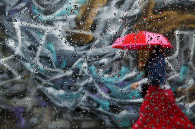 A woman walks past graffiti on a wall in the Williamsburg neighborhood of the borough of Brooklyn, in New York, September 16, 2014. The picture was taken through car window with raindrops. (REUTERS/Shannon Stapleton)