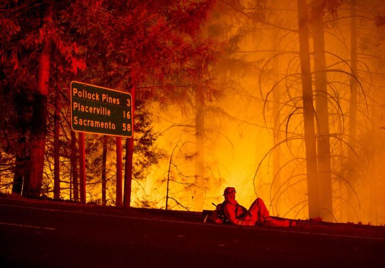 A firefighter battling the King Fire watches a backfire burn along Highway 50 in Fresh Pond, California on September 16, 2014. (REUTERS/Noah Berger)