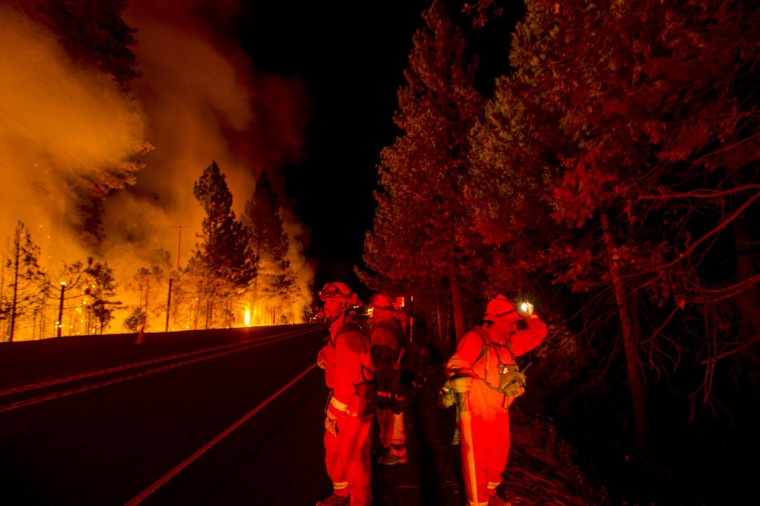 Inmate firefighters battling the King Fire watch for flying embers while a backfire burns along Highway 50 in Fresh Pond, California on September 16, 2014. (REUTERS/Noah Berger)