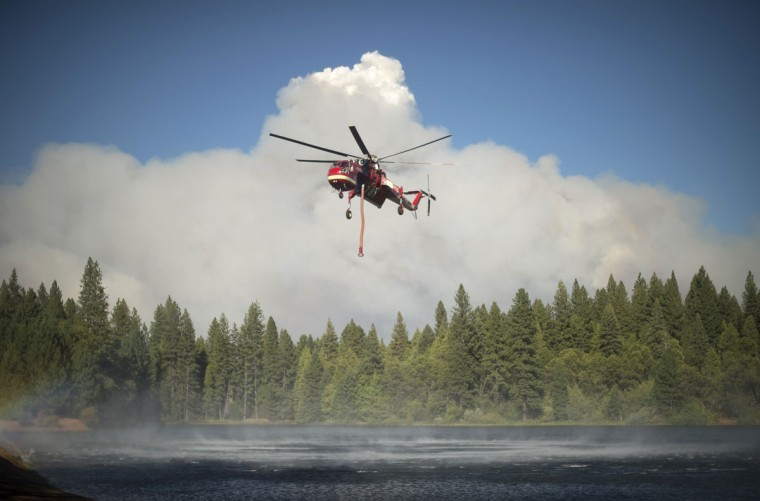 A helicopter draws water from a lake as smoke rises from the King Fire in Pollock Pines, California on September 17, 2014. (REUTERS/Noah Berger)