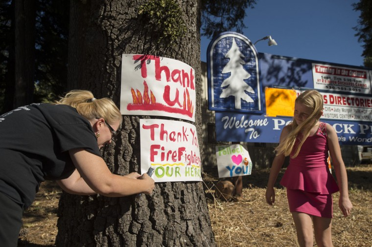 "Angela Warden displays a ""thank you"" sign for firefighters battling the King Fire in Pollock Pines, California on September 17, 2014. (REUTERS/Noah Berger)"