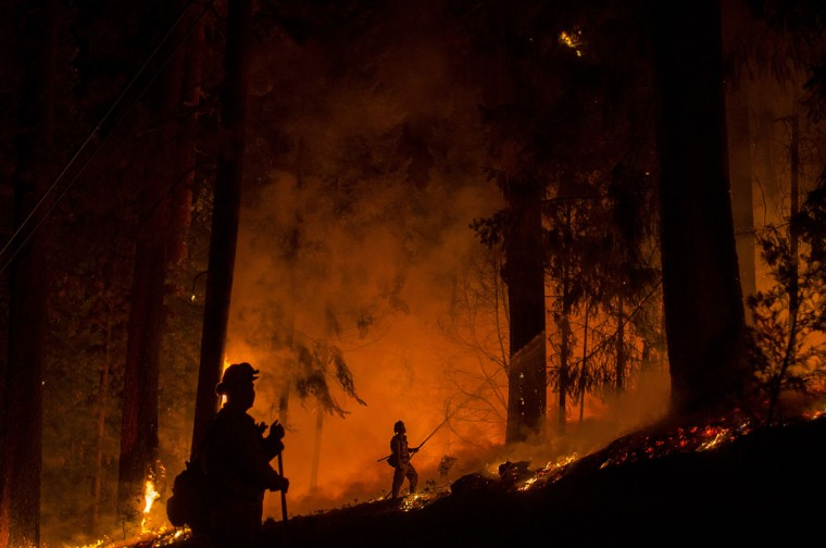 A firefighter battling the King Fire sprays water on a backfire in Fresh Pond, California on September 17, 2014. (REUTERS/Noah Berger)