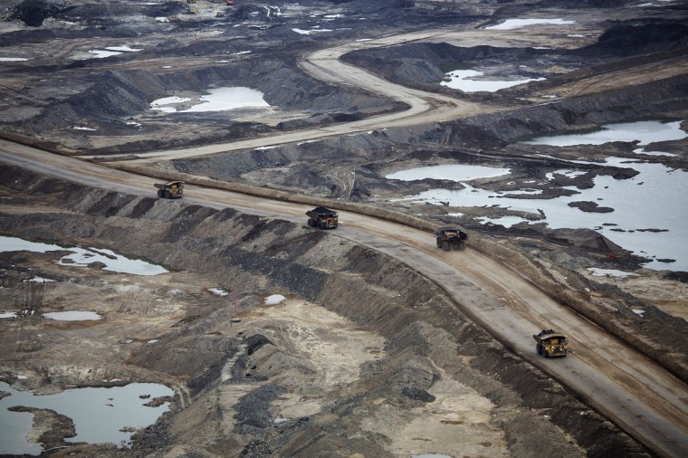Giant dump trucks haul raw tar sands at the Suncor tar sands mining operations near Fort McMurray, Alberta. In 1967 Suncor helped pioneer the commercial development of Canada's oil sands, one of the largest petroleum resource basins in the world. Picture taken September 17, 2014. (REUTERS/Todd Korol)