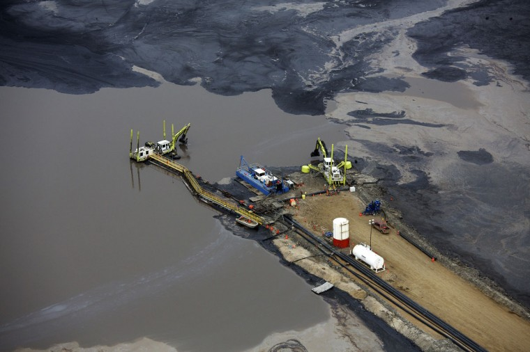 Heavy equipment works on a tailings pond at the Suncor tar sands operations near Fort McMurray, Alberta. In 1967 Suncor helped pioneer the commercial development of Canada's oil sands, one of the largest petroleum resource basins in the world. Picture taken September 17, 2014. (REUTERS/Todd Korol)