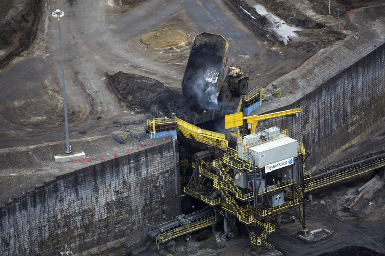 Giant dump trucks dump raw tar sands for processing at the Suncor tar sands mining operations near Fort McMurray, Alberta. In 1967 Suncor helped pioneer the commercial development of Canada's oil sands, one of the largest petroleum resource basins in the world. Picture taken September 17, 2014. (REUTERS/Todd Korol)
