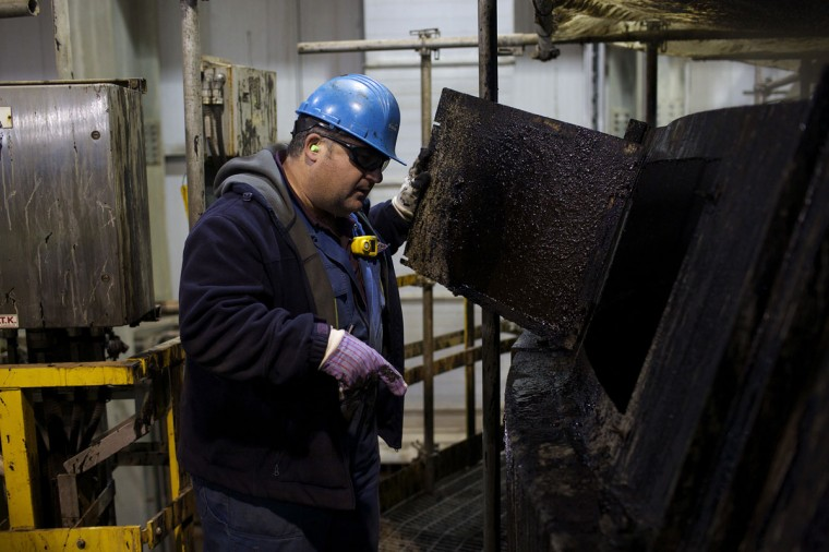 A Suncor oil worker checks an oil tank at the Suncor tar sands operations near Fort McMurray, Alberta. In 1967 Suncor helped pioneer the commercial development of Canada's oil sands, one of the largest petroleum resource basins in the world. Picture taken September 17, 2014. (REUTERS/Todd Korol)