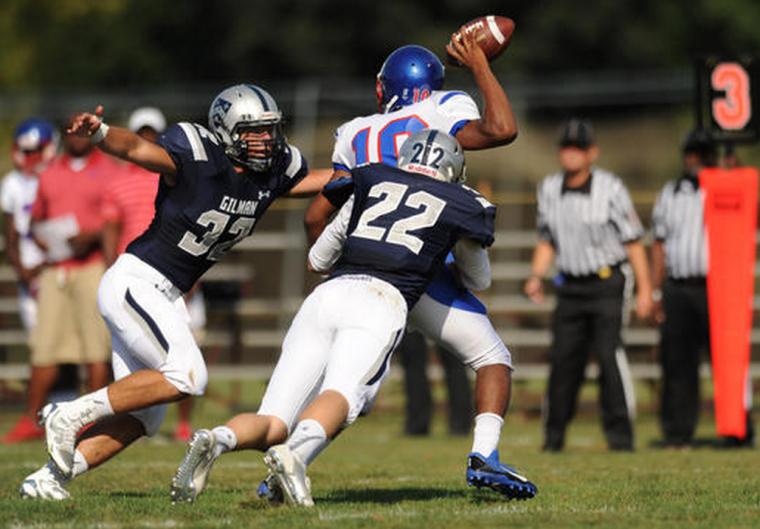 Anacostia quarterback Joe Moore barely gets a pass away as he's pressured by Gilman defenders Antonio DiCerbo, left, and John Fitzgerald. (Photo by Brian Krista, Baltimore Sun Media Group)
