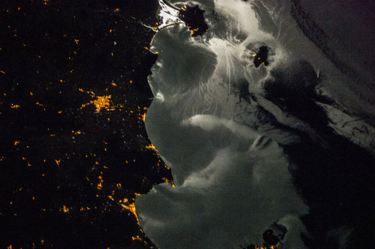This soft-focus image taken by a crewmember aboard the International Space Station during Expedition 37 shows the Elba-Follonica-Grosseto-Orbetello area of Italy at night, with moonglint on the surrounding waters. (NASA)