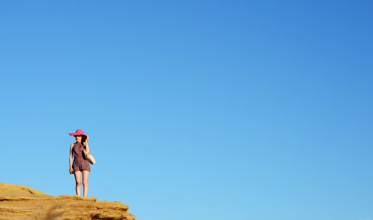 A woman holds onto her hat standing on the edge of a cliff at Sunset Cliffs.