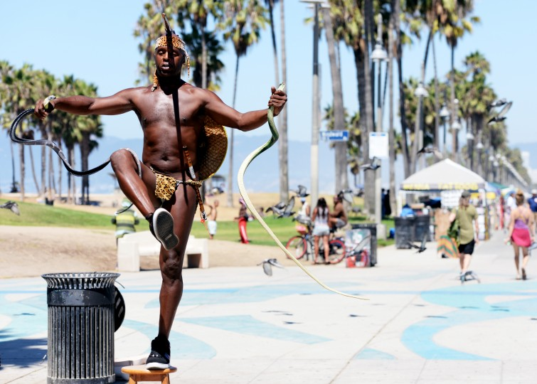 A street performer with two rubber snakes balances on a stool at the Venice Beach Boardwalk.