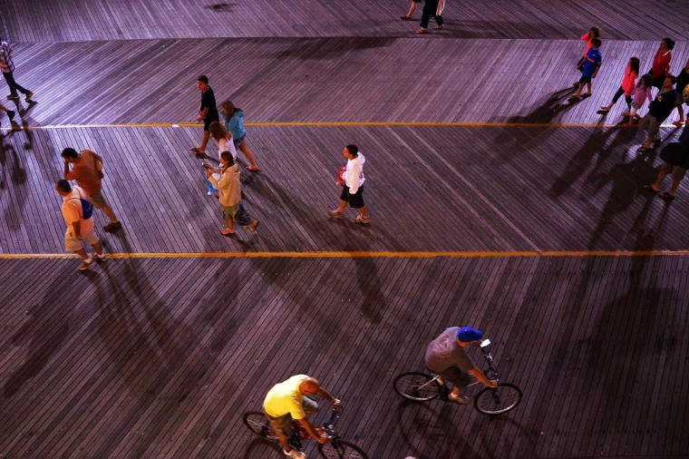 People walk on the boardwalk in Atlantic City on July 29, 2014 in Atlantic City, New Jersey. As neighboring cities open gambling businesses, fewer people are traveling to Atlantic City for visits to casinos. (Photo by Spencer Platt/Getty Images)
