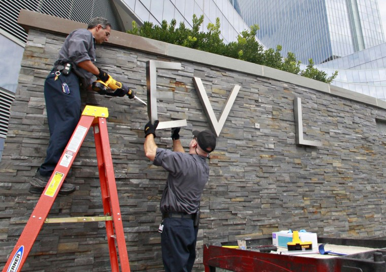 Joe Luccathetti (L) and Robert Fitting, employees of the Revel Casino Hotel remove signage from its wall along the boardwalk in Atlantic City, New Jersey September 1, 2014. (Tom Mihalek/Reuters)