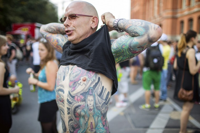 "A man lifts his T-shirt to show his tattoos during a parade, called something that cannot be printed, in Berlin. About a thousand people attended the annual summer event, which was founded in 1997 as a non-commercial counter-demonstration to the ""Love Parade"". (Hannibal Hanschke/Reuters)"