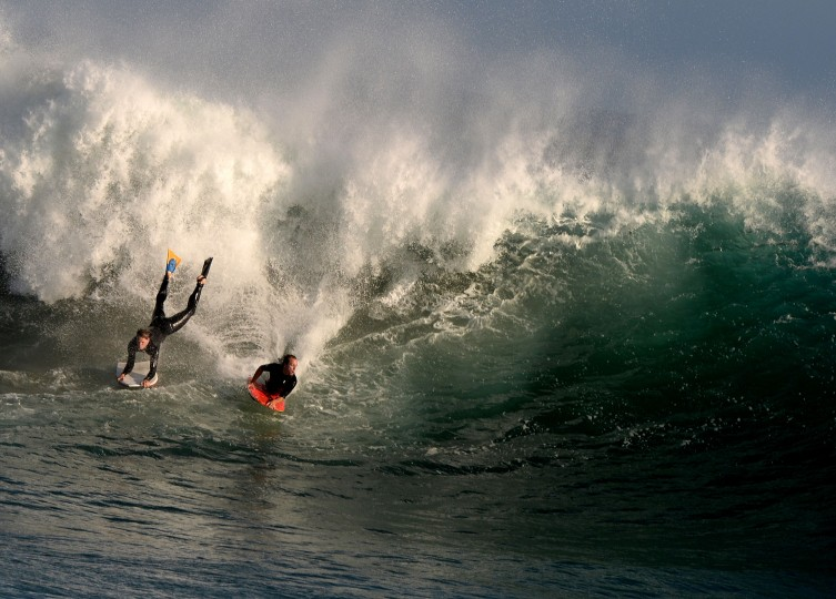 "Bodyboarders ride storm generated waves at ""The Wedge' break in Newport Beach, California. The southern Californian coast is being hit by its second set of large swells in 10 days, this time being generated by Cyclone Norbert. (Mark Ralston/AFP-Getty Images)"