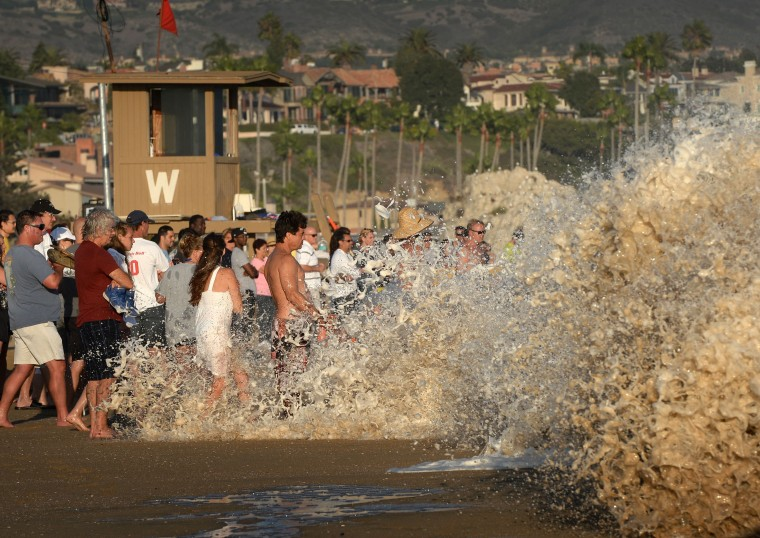 "A crowd is swamped by whitewash as they watch surfers ride storm generated waves at ""The Wedge"" break in Newport Beach. The southern Californian coast is being hit by its second set of large swells in 10 days, this time being generated by Cyclone Norbert. (Mark Ralston/AFP-Getty Images)"