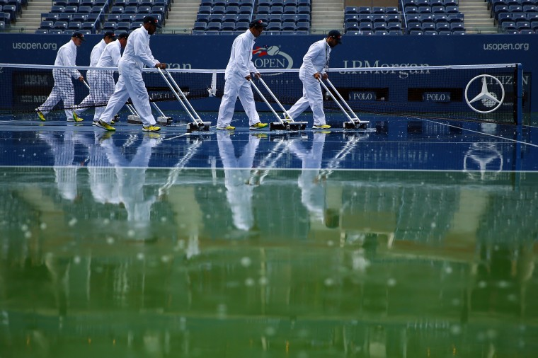 Grounds crew members attempt to dry the court during a rain delay on Day Thirteen of the 2014 US Open at the USTA Billie Jean King National Tennis Center in the Flushing neighborhood of the Queens borough of New York City. (Al Bello/Getty Images)
