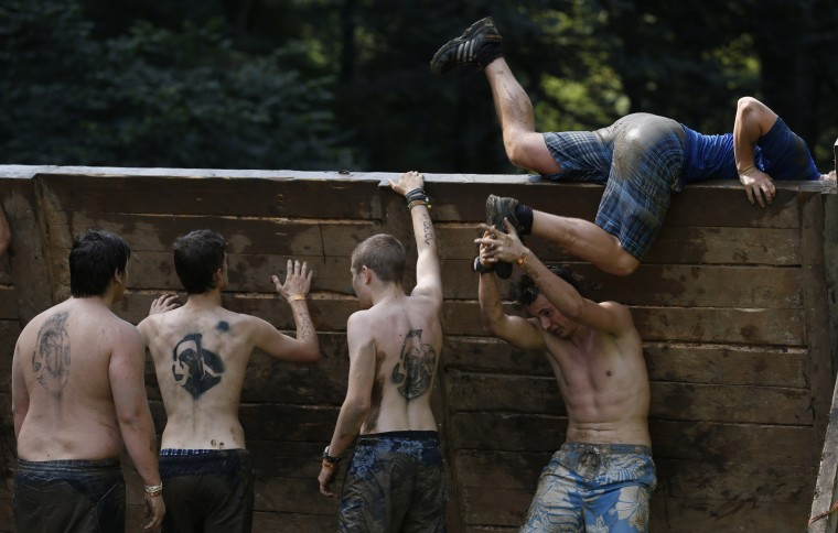 "Participants climb over a wall at the ""Tough Mudder"" endurance event series in Arnsberg. Competitors who took part in the endurance event saw themselves having to overcome various military style obstacles. (Ina Fassbender/Reuters)"