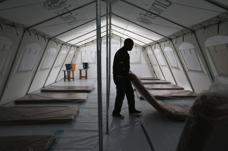 Workers prepare the new Doctors Without Borders (MSF), Ebola treatment center on August 17, 2014 near Monrovia, Liberia. The facility initially has 120 beds, making it the largest such center for Ebola treatment and isolation in history, and MSF plans to expand it to a 350-bed capacity. Tents at the center were provided by UNICEF. The Ebola epidemic has killed more than 1,000 people in four African countries, and Liberia now has had more deaths than any other country. (Photo by John Moore/Getty Images)