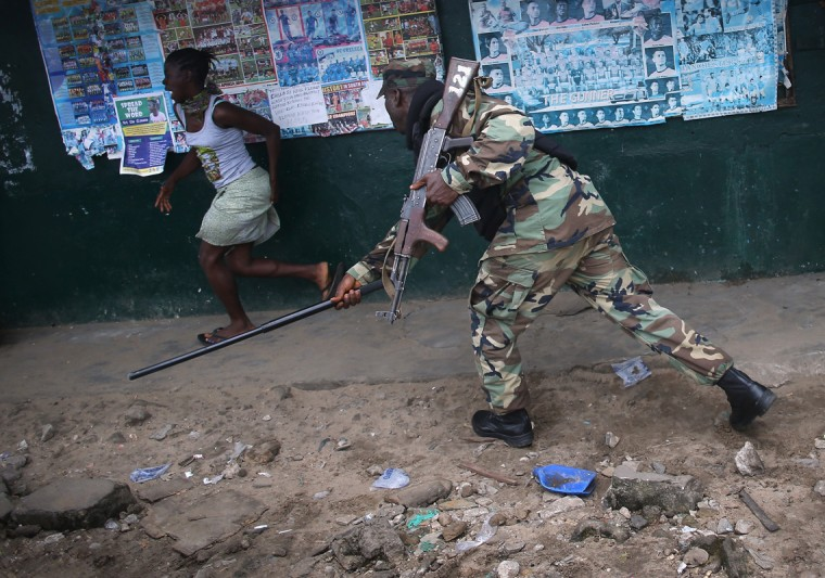 A Liberian Army soldier, part of the Ebola Task Force, beats a local resident while enforcing a quarantine on the West Point slum on August 20, 2014 in Monrovia, Liberia. The government ordered the quarantine of West Point, a congested seaside slum of 75,000, on Wednesday, in an effort to stop the spread of the virus in the capital city. Liberian soldiers were also sent in to the seaside favela to extract West Point Commissioner Miata Flowers and her family members after residents blamed the government for setting up a holding center for suspected Ebola patients to be set up in their community. A mob overran and closed the facility on August 16. The military also began enforcing a quarrantine on West Point, a congested slum of 75,000, fearing a spread of the epidemic. The Ebola virus has killed more than 1,200 people in four African nations, more in Liberia than any other country. (Photo by John Moore/Getty Images)