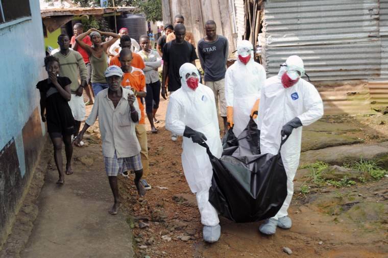 Health workers remove the body of Prince Nyentee, a 29-year-old man whom local residents said died of Ebola virus in Monrovia September 11, 2014. (James Giahyue/Reuters)