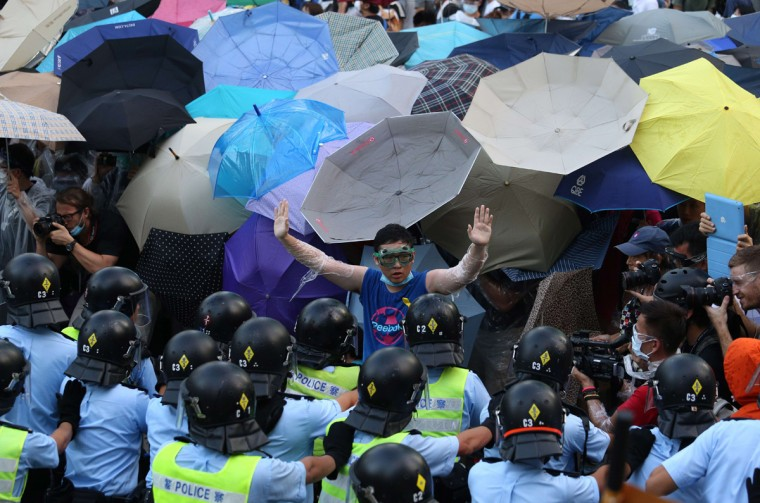 A pro-democracy demonstrator (C) gestures in front of a police line near the Hong Kong government headquarters on September 28, 2014. Police fired tear gas as tens of thousands of pro-democracy demonstrators brought parts of central Hong Kong to a standstill Sunday, in a dramatic escalation of protests that have gripped the semi-autonomous Chinese city for days. (Aaron Tam/AFP/Getty Images)