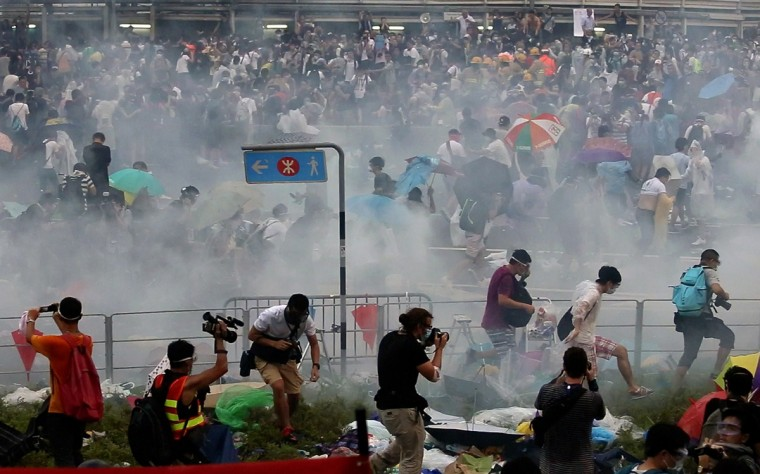 People disperse after police fired tear gas upon pro-democracy demonstrators near the Hong Kong government headquarters on September 28, 2014. Police fired tear gas as tens of thousands of pro-democracy demonstrators brought parts of central Hong Kong to a standstill on September 28, in a dramatic escalation of protests that have gripped the semi-autonomous Chinese city for days. (Aaron Tam/AFP/Getty Images)