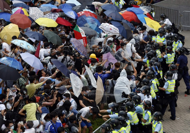 Protesters take cover from pepper spray with umbrellas as riot police clash with tens of thousands of protesters blocking the main street leading to the financial Central district outside the government headquarters in Hong Kong September 28, 2014. The leader of a Hong Kong movement seeking greater democracy announced in the early hours of Sunday the launch of a campaign to blockade the heart of the financial centre to demand greater freedoms in the former British colony. (Bobby Yip/Reuters)